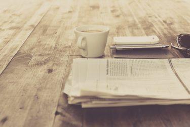 Zeitung, Tasse, Handy, Stift und Brille