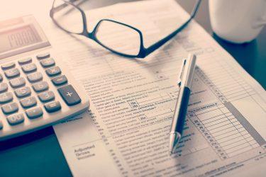 Taschenrechner, Formular, Kugelschreiber und Brille